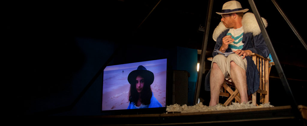 A seated actor wearing hat and coat with a fur collar looks to his right at a screen showing a teenage girl stood on a beach.